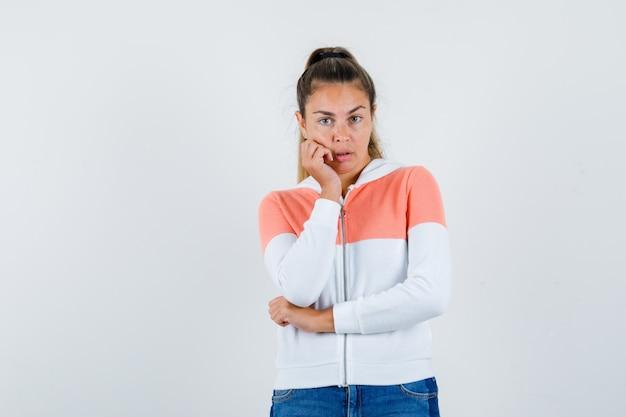 Jovem, com a bochecha apoiada na palma da mão, usando um capuz com zíper, jeans e uma aparência fofa