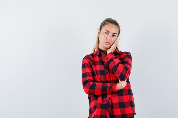 Jovem com a mão na bochecha com uma camisa xadrez e parecendo pensativa