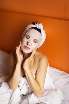 Jovem com a pele limpa com uma máscara no rosto, deitada na cama, descansando depois do banho, relaxando em casa. fechar-se.