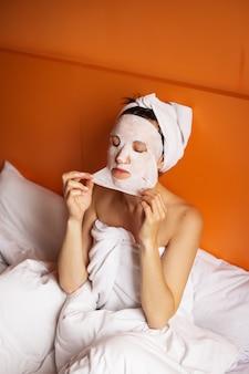 Jovem com a pele limpa com uma máscara no rosto, sentada na cama, descansando depois do banho, relaxando em casa. fechar-se.