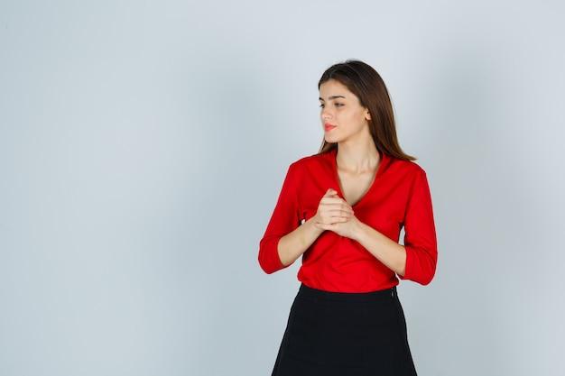 Jovem com as mãos cruzadas no peito enquanto desvia o olhar com uma blusa vermelha