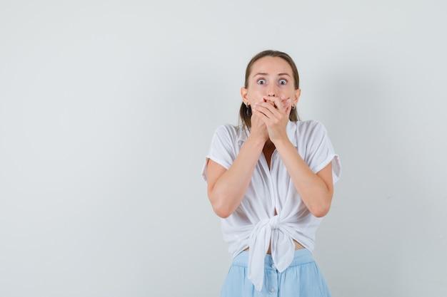 Jovem com as mãos na boca com blusa e saia e parecendo assustada