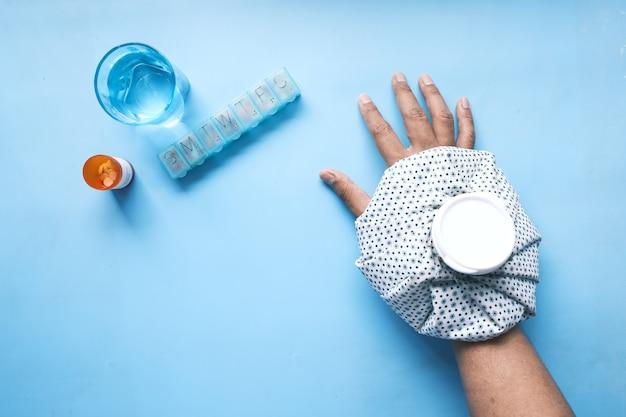 Jovem com as mãos sofrendo de dor no pulso e aplicando água fria no local da lesão