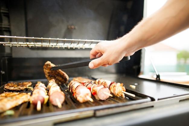 Jovem com as mãos virando a carne com um garfo na churrasqueira a gás