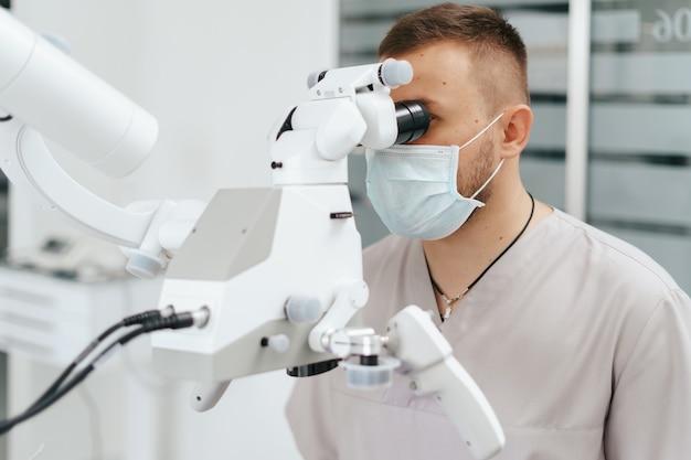 Jovem com babador de paciente em uma cadeira odontológica e um dentista que se senta ao lado dele. ele olha para os dentes usando um microscópio odontológico e segura uma broca odontológica e um espelho.