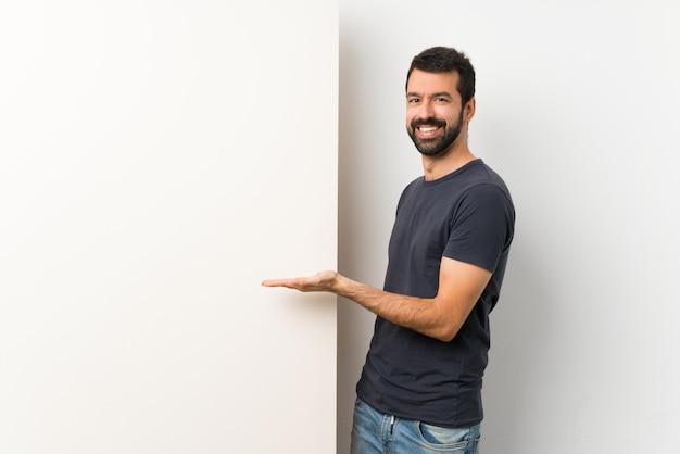 Jovem com barba, apresentando algo