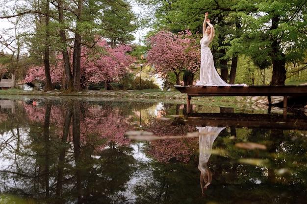 Jovem com barba e noiva em vestido longo luxo, abraçando-se perto do lago no parque com cereja desabrocham ou sakura floresce. dia de primavera casamento