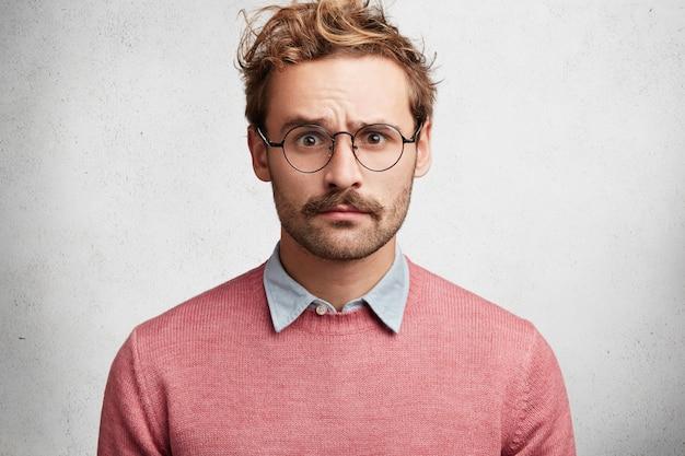 Jovem com barba e óculos redondos