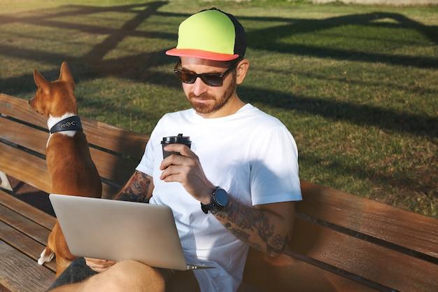 Jovem com barba e tatuagens, vestindo uma camiseta branca lisa, bebendo café e olhando para seu laptop, enquanto seu cachorro marrom e branco está sentado ao lado dele em um banco do parque.