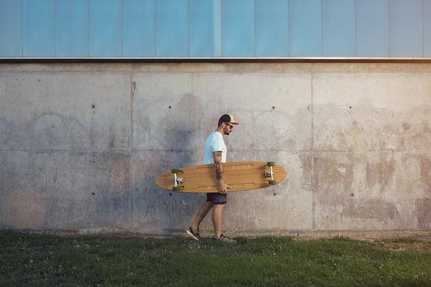 Jovem com barba e tatuagens vestindo uma camiseta branca lisa, shorts, tênis e boné de beisebol carregando um longboard ao longo de uma parede de concreto