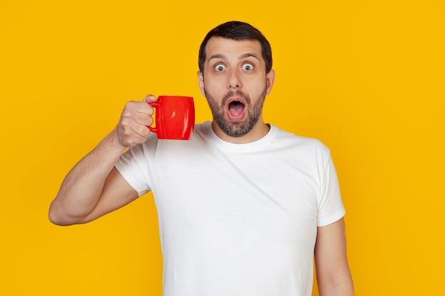 Jovem com barba em uma camiseta branca bebe uma xícara de café, assustado em estado de choque com uma cara de surpresa, assustado e excitado com uma expressão de medo.