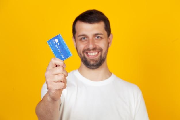 Jovem com barba em uma camiseta branca, segurando um cartão de crédito com uma cara feliz, se levanta e sorri com um sorriso confiante, mostrando os dentes.