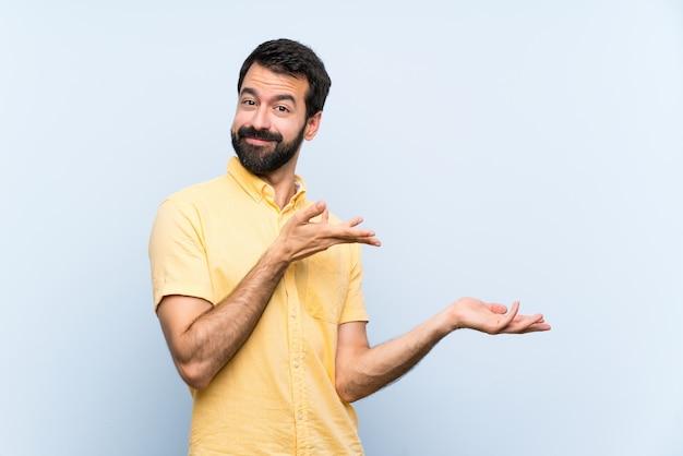 Jovem com barba isolado azul, estendendo as mãos para o lado por convidar para vir