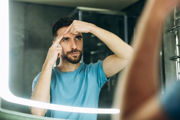 Jovem com barba na camiseta azul, apertando a espinha no espelho do banheiro, problema de acne.
