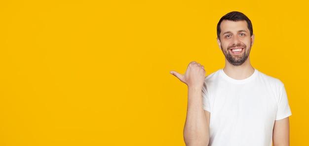 Jovem com barba na cara feliz de t-shirt branca, sorrindo com cara feliz, olhando e apontando para o lado com o polegar para cima.