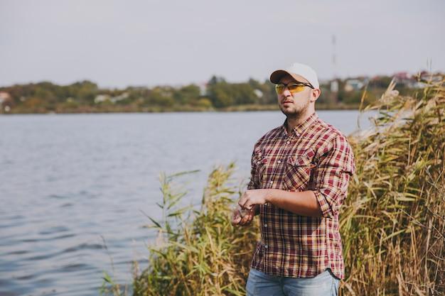 Jovem com barba por fazer em óculos de sol, boné e camisa quadriculada parece longe e tira uma pequena caixa de isca de larva para pescar num contexto de lago, arbustos, juncos. estilo de vida, conceito de lazer do pescador.
