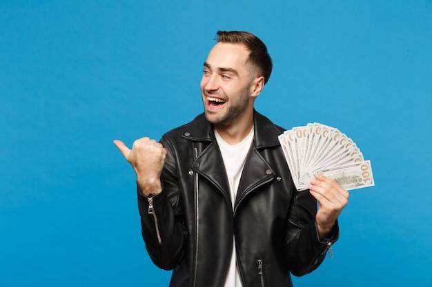 Jovem com barba por fazer em t-shirt branca de jaqueta de couro preta segurando leque de dinheiro em notas de dólar isoladas no retrato de estúdio de fundo de parede azul. conceito de estilo de vida de pessoas. simule o espaço da cópia.