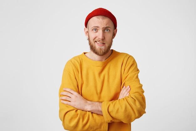 Jovem com barba ruiva, usando chapéu e um suéter amarelo, com os braços cruzados, parece cético