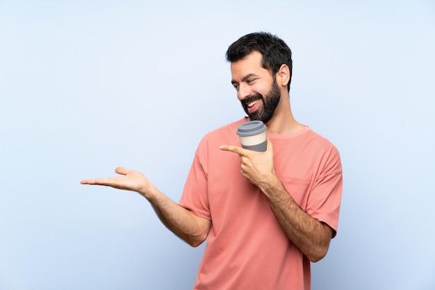 Jovem com barba segurando um café para viagem isolado parede azul segurando copyspace imaginário na palma da mão para inserir um anúncio