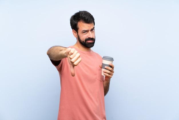 Jovem, com barba, segurando um café para viagem sobre parede azul isolada, mostrando o polegar para baixo com expressão negativa