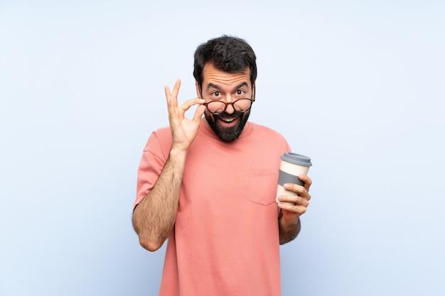 Jovem, com barba, segurando um café take away sobre parede azul isolada com óculos e surpreso