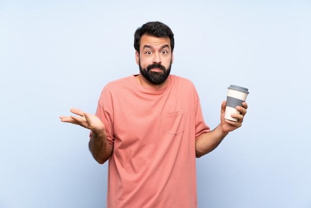 Jovem, com barba, segurando um café take away sobre parede azul isolada, fazendo o gesto de dúvidas