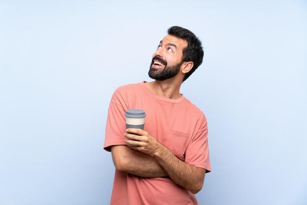 Jovem, com barba, segurando um café take away sobre parede azul isolada, olhando para cima enquanto sorrindo