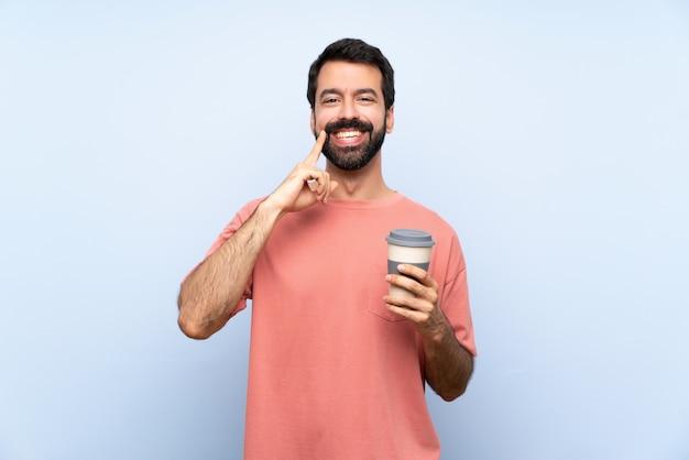 Jovem, com barba, segurando um café take away sobre parede azul isolada, sorrindo com uma expressão feliz e agradável