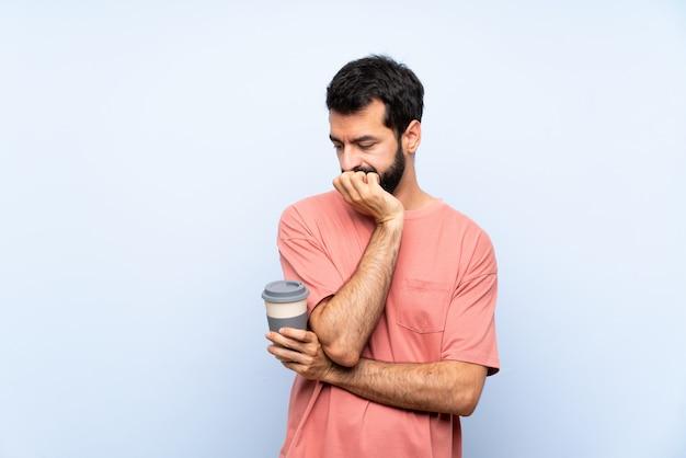 Jovem, com barba, segurando um café take away sobre parede azul isolada, tendo dúvidas