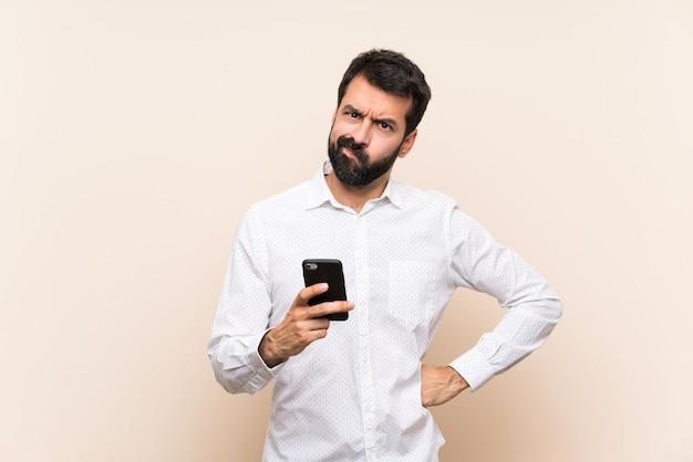 Jovem, com barba, segurando um celular com raiva