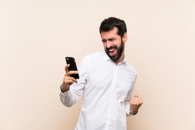 Jovem, com barba, segurando um celular com telefone em posição de vitória