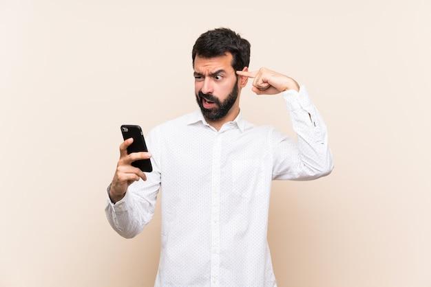 Jovem, com barba, segurando um celular, fazendo o gesto de loucura, colocando o dedo na cabeça