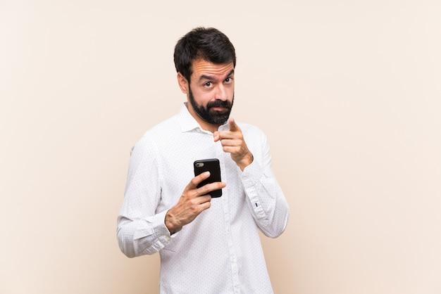 Jovem com barba segurando um celular frustrado e apontando para a frente