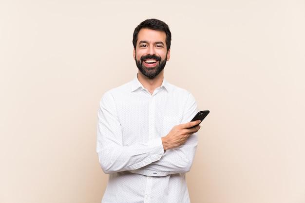 Jovem, com barba, segurando um celular, mantendo os braços cruzados na posição frontal