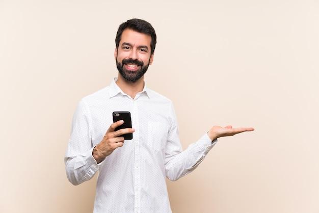 Jovem com barba segurando um celular segurando copyspace imaginário na palma da mão para inserir um anúncio