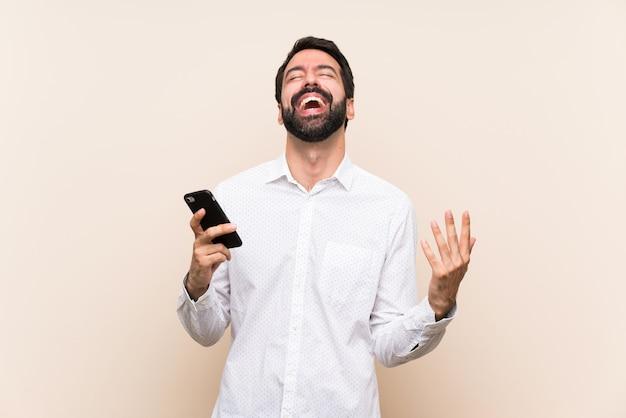 Jovem, com barba, segurando um celular sorrindo muito