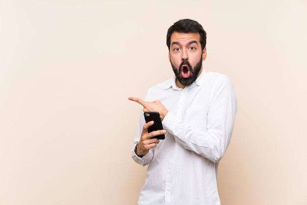 Jovem, com barba, segurando um celular surpreso e apontando o lado