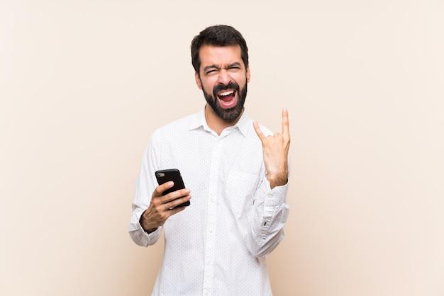 Jovem, com barba, segurando um móvel fazendo gesto de pedra