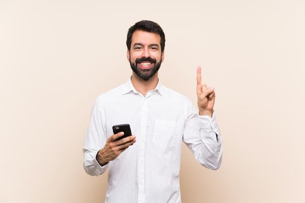Jovem, com barba, segurando um móvel mostrando e levantando um dedo em sinal dos melhores