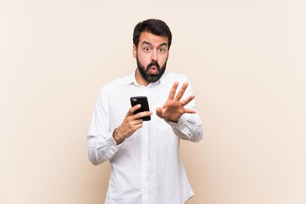 Jovem, com barba, segurando um móvel nervoso, esticando as mãos para a frente