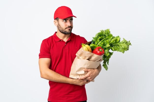 Jovem com barba segurando uma sacola cheia de vegetais isolados na parede branca pensando em uma ideia