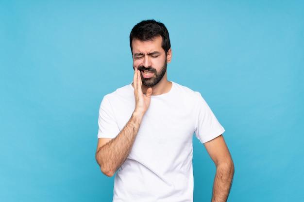 Jovem com barba sobre azul isolado com dor de dente