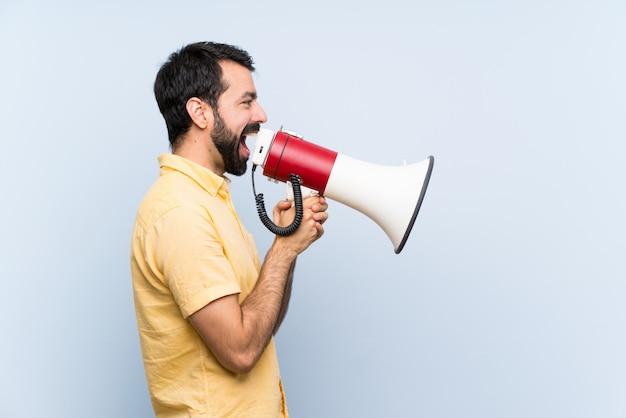 Jovem com barba sobre azul isolado gritando através de um megafone