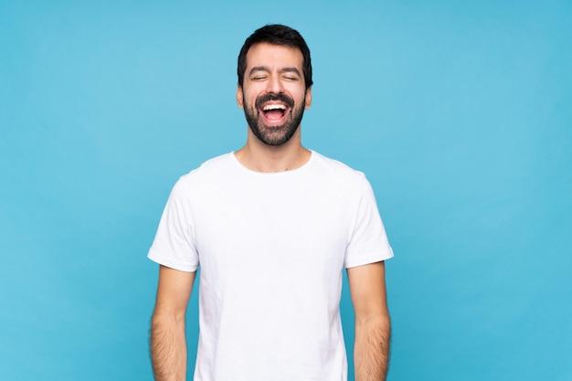 Jovem com barba sobre azul isolado gritando para a frente com a boca aberta