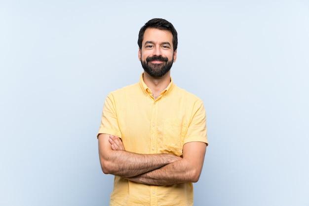 Jovem com barba sobre azul isolado, mantendo os braços cruzados na posição frontal