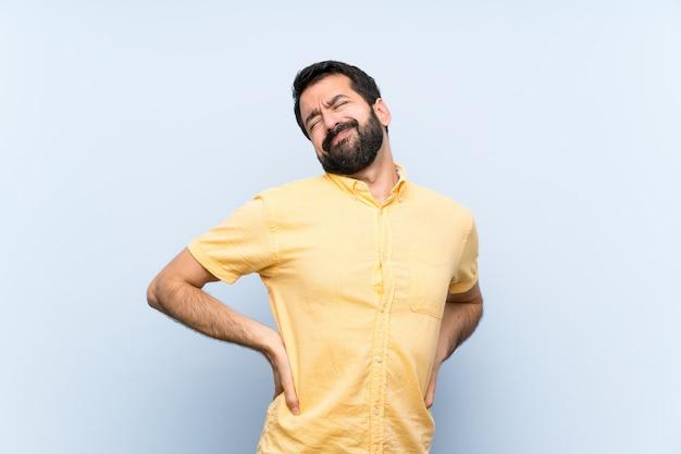 Jovem com barba sobre azul isolado, sofrendo de dor nas costas por ter feito um esforço