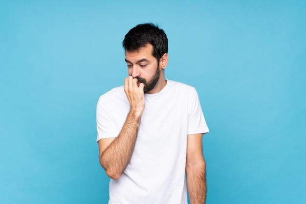 Jovem com barba sobre azul isolado tendo dúvidas