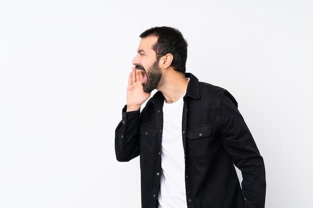 Jovem com barba sobre branco isolado gritando com a boca aberta para a lateral