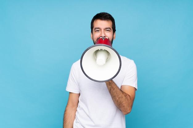 Jovem com barba sobre fundo azul isolado, gritando através de um megafone
