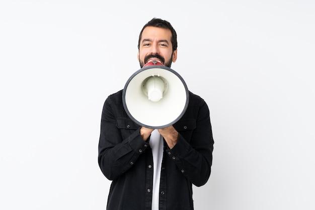Jovem com barba sobre fundo branco isolado, gritando através de um megafone